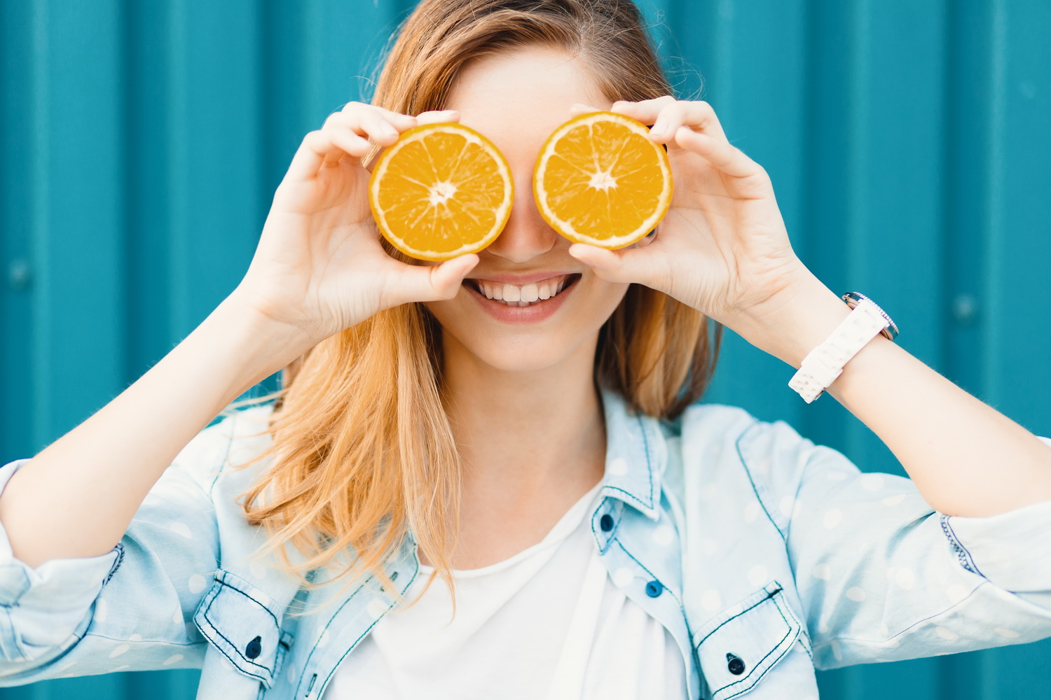 Carefree young beautiful girl using two halfs on oranges instead of glasses over her eyes